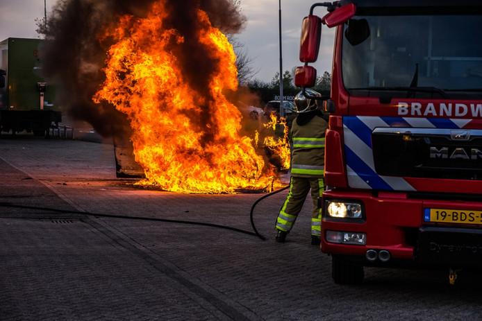 De brandweer bezig met het blussen van de brandende auto.