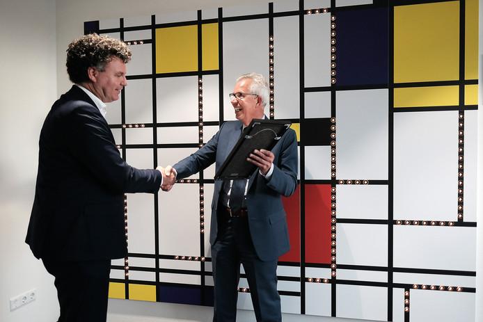 Burgemeester Thijs van Beem (rechts) ontvangt het Mondriaan-kunstwerk van SKB-directeur Bert Kleinlugtenbeld.