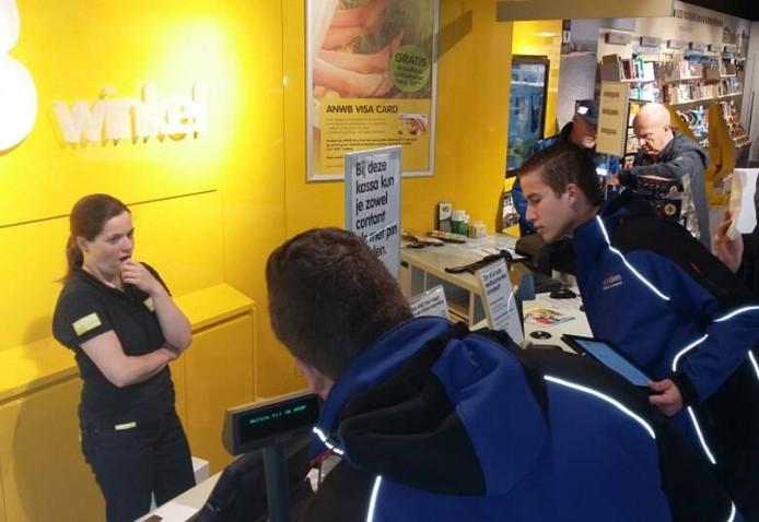 Leerlingen van RijnIJssel controleren de balie van de nieuwe Arnhemse ANWB-winkel.