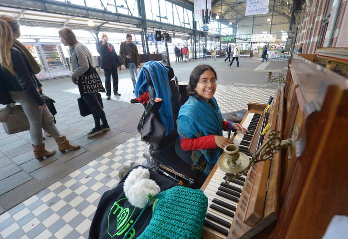 Rhea Elise Khoeblal in de Nijmeegse stationshal. Op haar initiatief werd hier een oude piano neergezet waarop iedereen mag spelen.