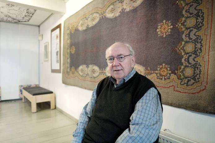 Rinus Rabeling voor een tapijt van de ontwerper Theo Colenbrander in de salon van museum De Roode Tooren.