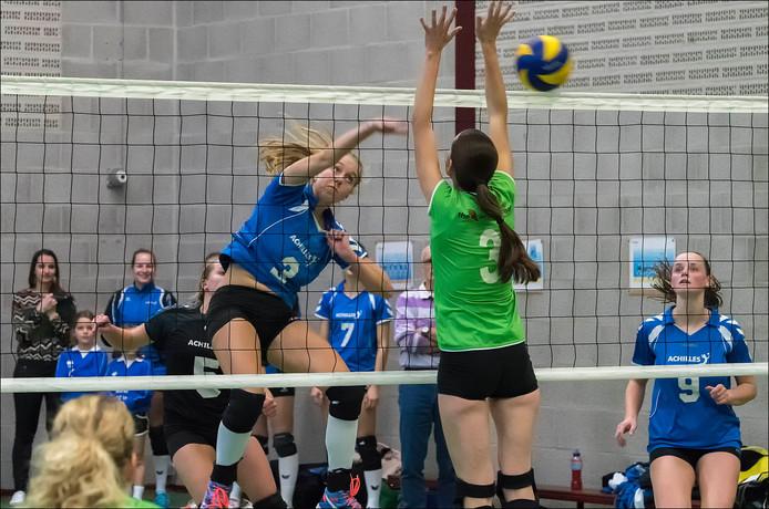 Achilles-speelster Evelien Jansen smasht de bal langs het eenmansblok van Sittardia.