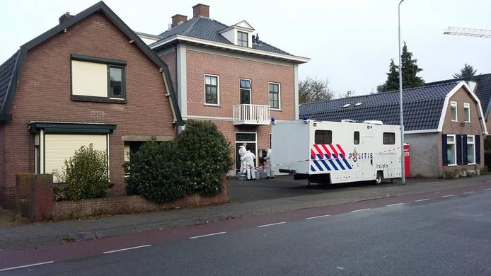 Mannen in witte pakken onderzoeken de woning aan de Veenderweg in Ede waar de verdachte woont. Foto: DG