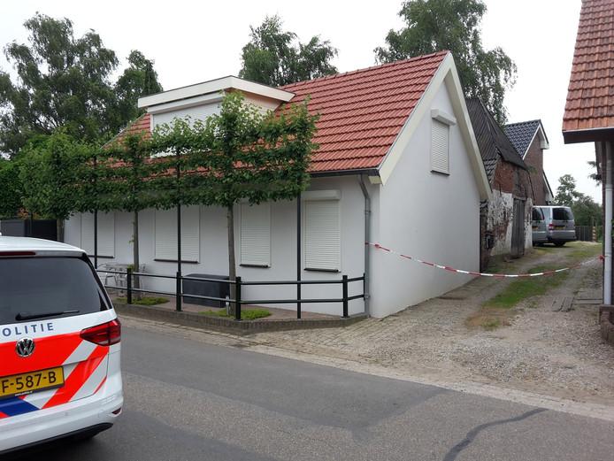 De grijze busjes van de recherche staan op de oprit van het huis waar de steekpartij was.