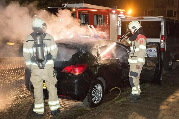 De brandweer bezig met het blussen van de brandende Opel.