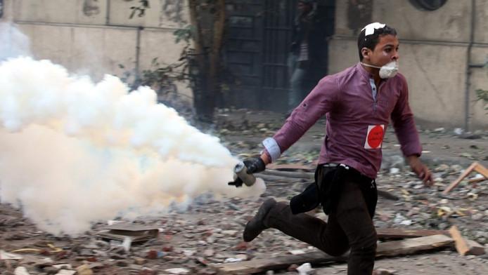 Een jongen rent weg met een traangasgranaat