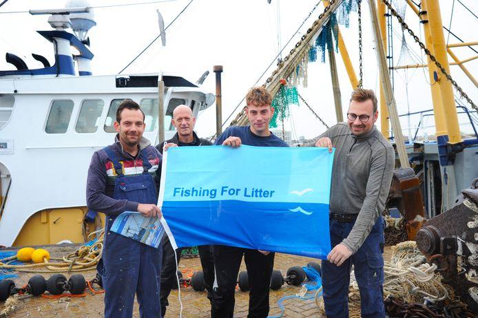 Schipper Henry Caljouw van de ARM 46 (links) houdt met broers en bemanningsleden Wesley en Jordy de vlag van Fishing for Litter vast. Op de achtergrond (tweede van links) Rudy Marinisse, wiens bedrijf de vismijn helpt met het ophalen van big bags met afval.