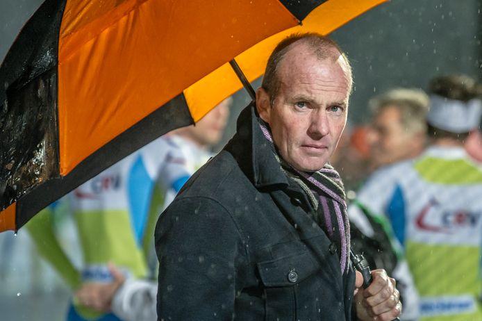 Oud-winnaar van de Elfstedentocht Henk Angenent met paraplu langs de schaatsbaan.