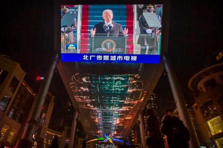 De inauguratie van Joe Biden was woensdag ook te zien op een groot scherm in een winkelcentrum in Peking.  Beeld AP