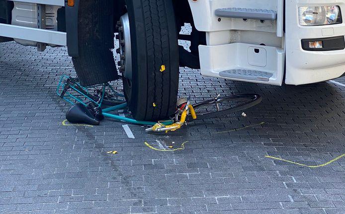 De fiets ligt onder het zware wiel van de vrachtwagen.