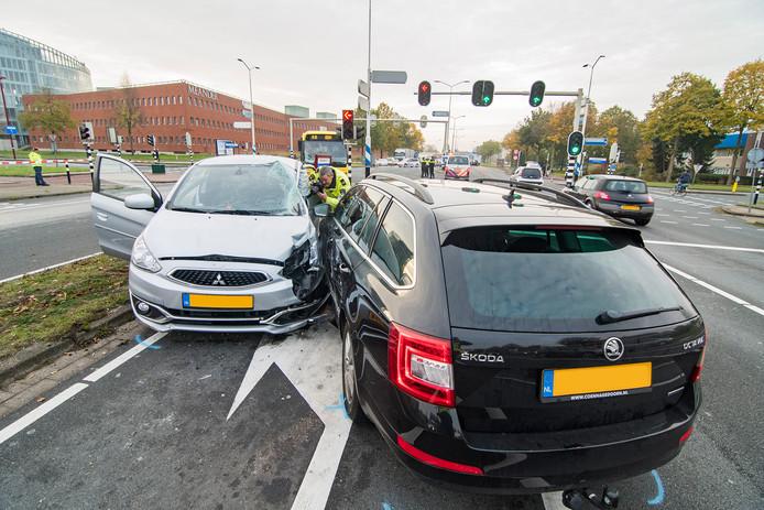 Flinke schade aan twee voertuigen, nadat één van de twee auto's in botsing kwam met een stadsbus, die op de achtergrond staat.
