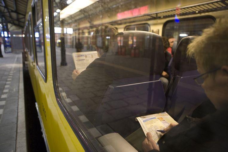 Een vrouw lost een Sudoku-puzzel op in de trein. Beeld Harry Cock