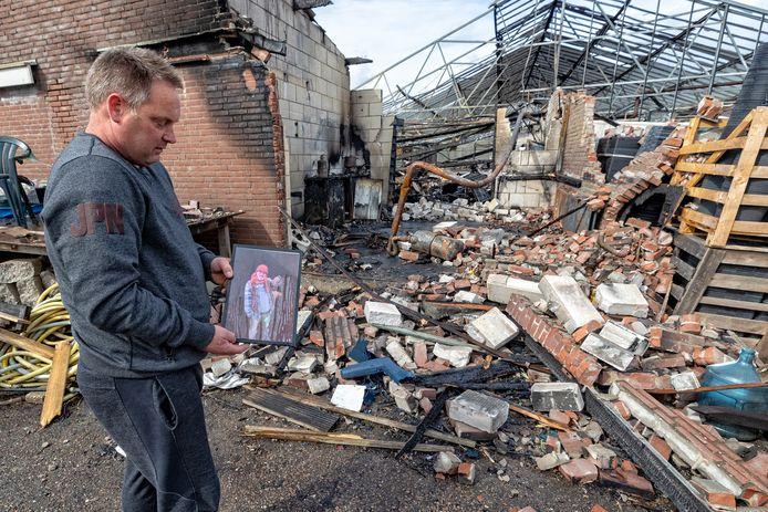 Arno van Vliet bij de restanten van de brand in zijn loods. Hans Moggré, die hier tijdelijk mocht verblijven, is bij de brand om het leven gekomen.