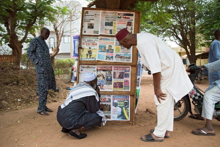 Mannen in de Malinese hoofdstad Bamako kijken naar de koppen van kranten waarin Frankrijk aankondigt te stoppen met de Operatie Barkhane.   Beeld Hollandse Hoogte/AFP