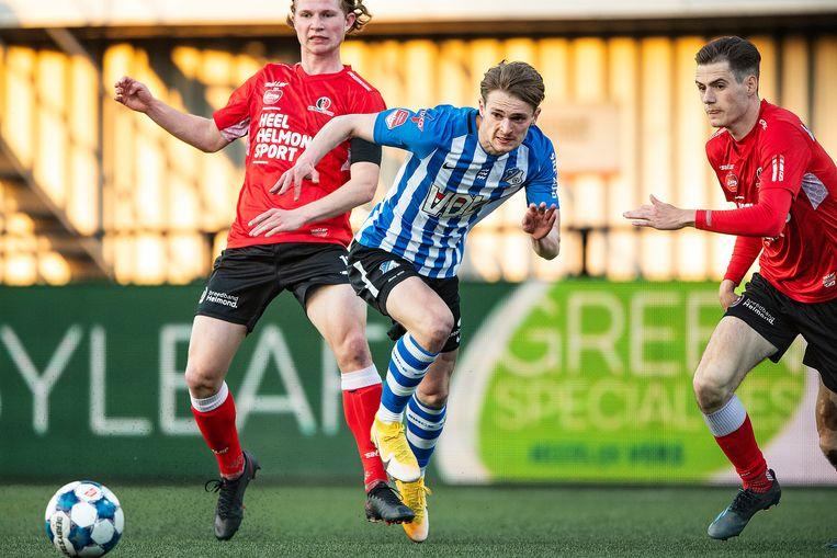 FC Eindhoven-speler Mitchel van Rosmalen passt de bal onder druk van Helmond-spelers Arno Van Keilegom en Sander Vereijken. Beeld  Guus Dubbelman / de Volkskrant