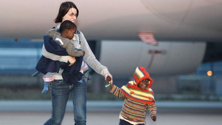 Een adoptiemoeder haalt twee adoptiekinderen op bij Eindhoven Airport. 106 kinderen werden in 2010 in Nederland opgevangen na de aardbeving in Haïti. Beeld anp
