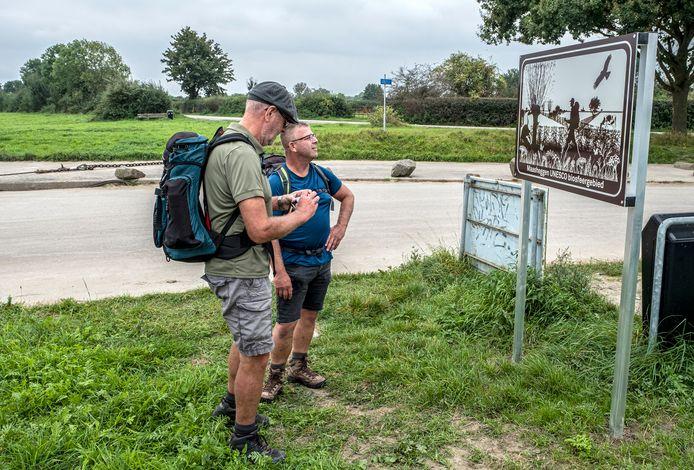 Wandelaars bij het bord aan de veerstoep van Sambeek, toegangspoort naar het Maasheggengebied.