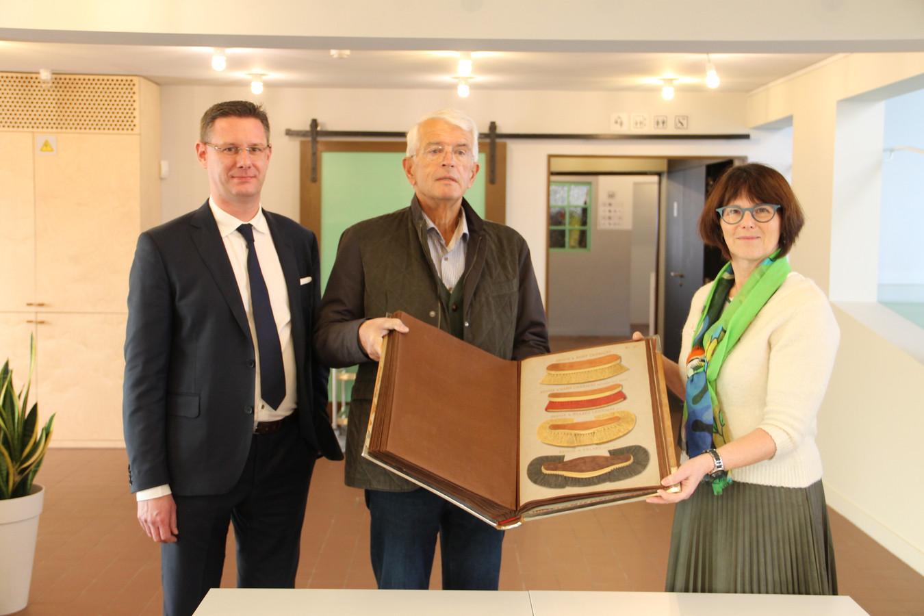 Carl Decoopman (midden) schenkt de borstelcatalogus aan conservator Hilde Colpaert en erfgoedschepen Kurt Himpe (N-VA).