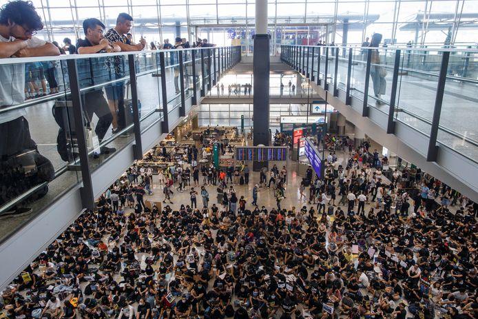 Honderden demonstranten bevolken de aankomsthal van Hongkong International Airport in Hongkong.