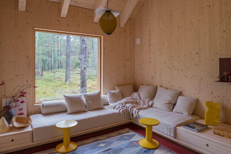 De grenenhouten banken van Halleroed zijn afgewerkt met linnen kussens en schapenvachtjes. De stoeltjes zijn vintage Fins, het tapijt is vintage Zweeds. Beeld Nin Solis