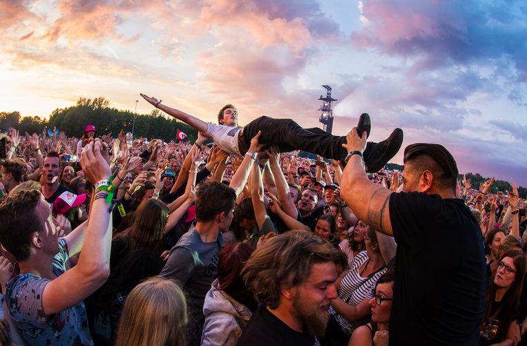 De Amerikaanse punkrockband Green Day treedt op tijdens de tweede dag van muziekfestival Pinkpop in 2017. Een fan zong een stukje mee en nam daarna een duik in het publiek. Beeld ANP Kippa