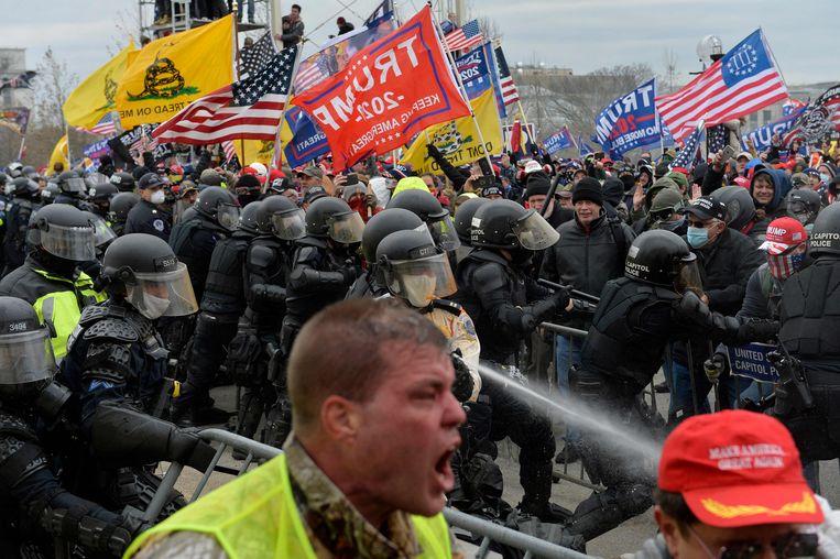 Aanhangers van de Amerikaanse oud-president Trump clashen op de dag van de bestorming met de politie en Nationale Garde aan het Capitool. Beeld AFP