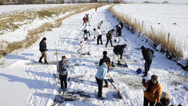 Tientallen vrijwilligers maken het ijs op de route van de Elfstedentocht bij Hindeloopen sneeuwvrij. © ANP Beeld