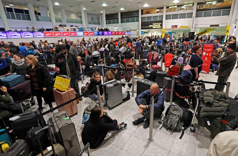 Honderden mensen die toch naar de luchthaven kwamen of er al waren, wachten in Gatwick tot de luchthaven opnieuw open kan gaan. Beeld REUTERS