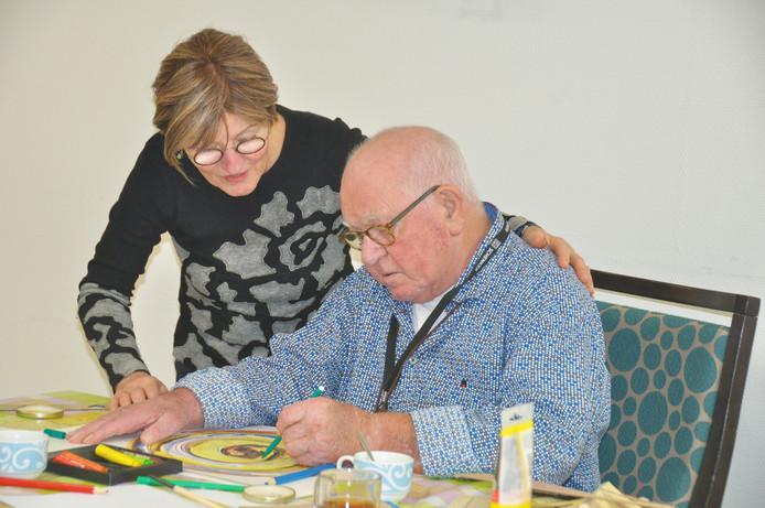Bewoner Antoon van den Hoven is geconcentreerd aan het werk. Begeleidster en kunstenares Marian van den Berg kijkt over zijn schouder mee.