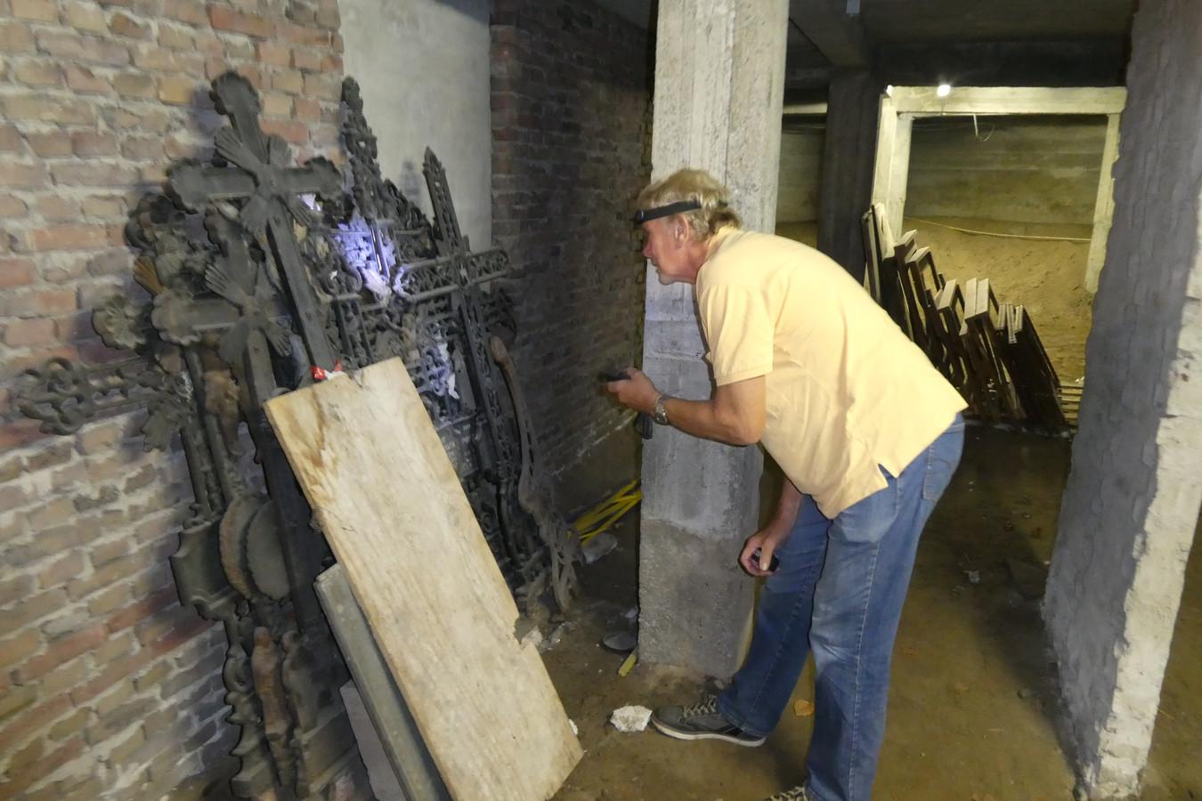 Jan Spit bekijkt de oude gietijzeren kruizen uit de negentiende eeuw in de kelder van de Michaëlkerk in Gestel.