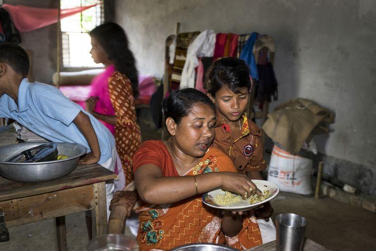 Parvin (29) en haar jongste dochter thuis in Sherpur, 200 kilometer ten noorden van Dhaka. Ze werkt in Dhaka en komt af en toe terug om haar kinderen te zien. Beeld Catrien Ariens