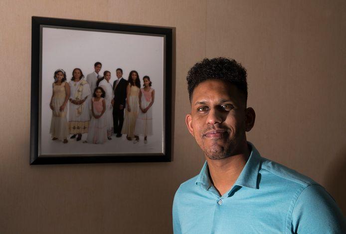 Meron Zehaye kwam als 9-jarig jochie vanuit Eritrea naar de Achterhoek. Op de achtergrond een familiefoto.
