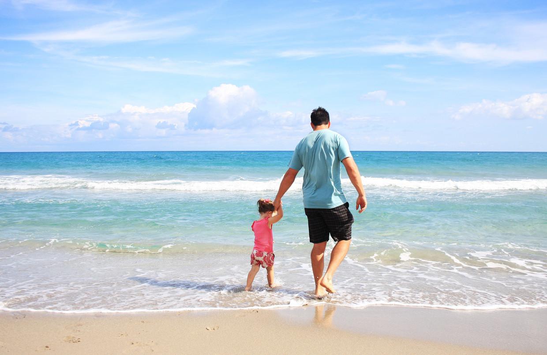 Vader en kind op het strand. Beeld Pexels
