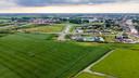 """Luchtfoto van de Steekterpoort waar een distributiecentrum moet komen. Linksboven containerterminal Alpherium en de N11. Centraal: de rotonde naar het afvalscheidingsstation De Limes. Helemaal rechts""""de Oude Rijn en Steekterweg."""