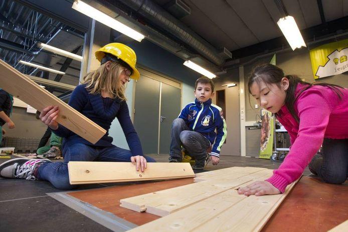 """Kim, Dylano en Alisa (vlnr) leggen samen een houten vloer. """"Hartstikke makkelijk, we waren zo klaar."""" foto René Manders"""