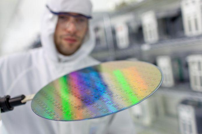 Een onderzoeker van Imec bekijkt een chipschijf.