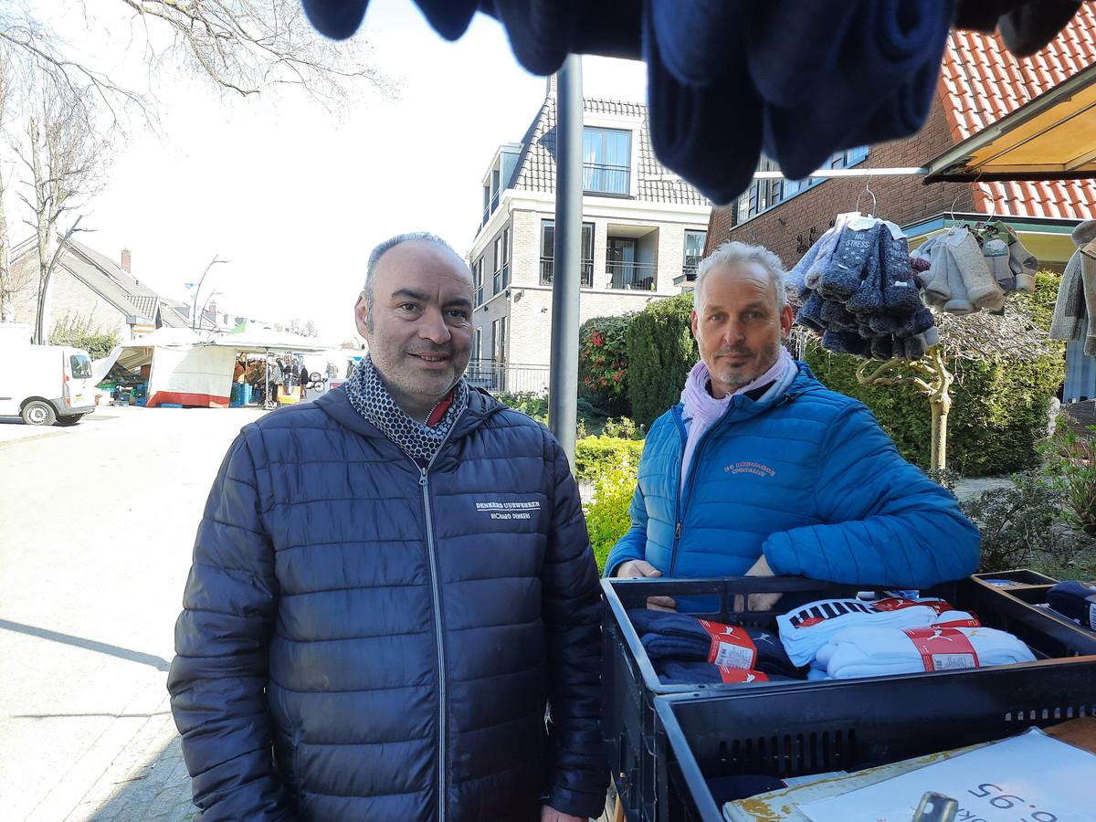 Marktkooplieden Richard Denkers (l) en Jan Lubbers bij de 'illegale sokkenkraam' op de markt in Voorthuizen. Op de achtergrond de gewone warenmarkt op zaterdagochtend.