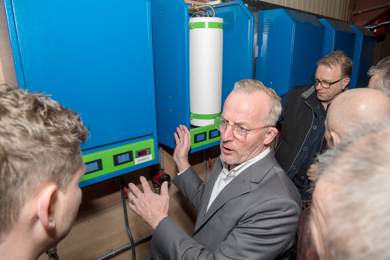 Wil Schottman poseert en legt uit bij de nieuwe duurzame ketels die hij uitvond.