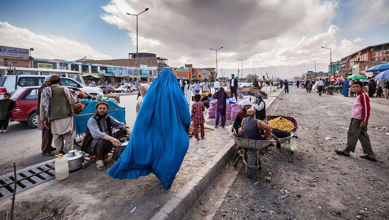 Afghanistan, Kabul, juni 2012. Een vrouw in burka haast zich door een straat in centrum Kabul waar allerhande producten op de stoep worden verkocht. Beeld Jeroen Swolfs