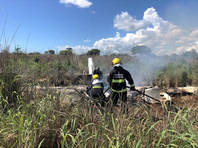 Enkele brandweerlui blussen het wrak van het neergestorte vliegtuig. Beeld EPA