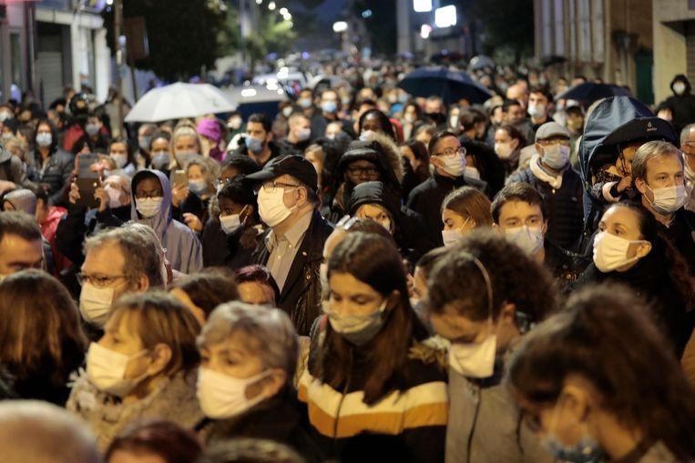 Mensen dinsdagavond in een mars die als eerbetoon wordt gehouden voor Samuel Paty, de leraar die vorige week vrijdag werd onthoofd.  Beeld AP