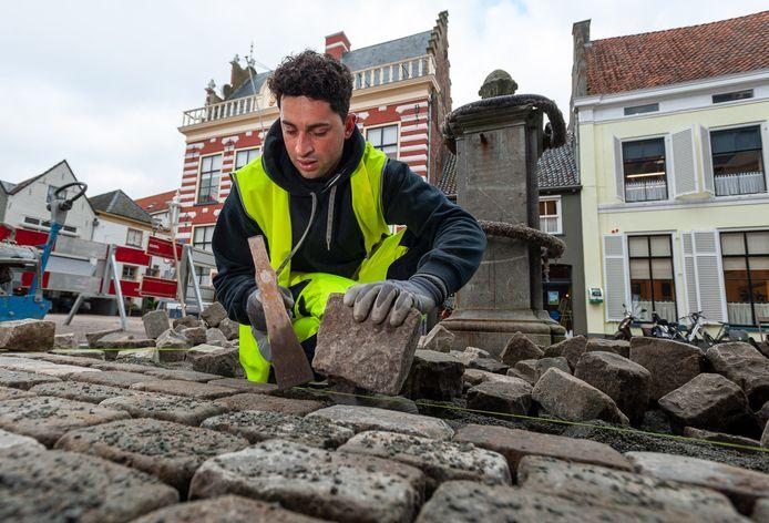 De Portugese stratenmaker Jose Francisco aan het werk in het centrum van Hattem.