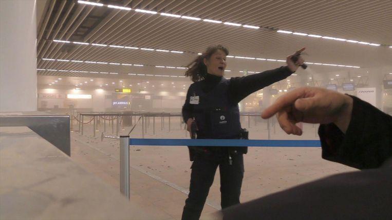 Een politieagente instrueert reizigers in een met rook gevulde terminal op de luchthaven van Brussel. Beeld ap