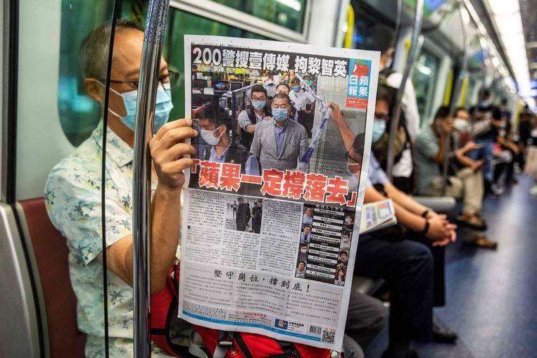Een passagier in de metro leest de Apple Daily die nu dreigt te verdwijnen. Beeld AFP