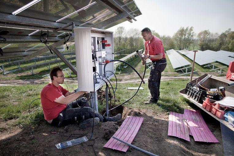 Elektriciens sluiten bedrading van zonnepanelen aan. Beeld Herman Engbers