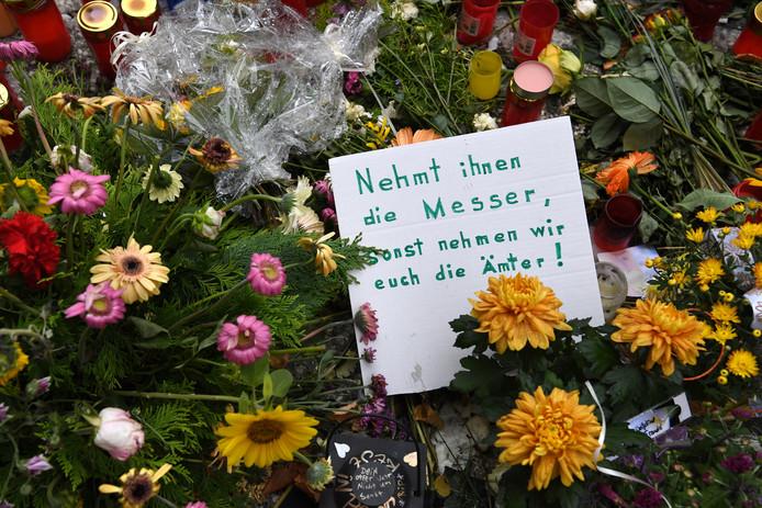 """Een stuk karton met de boodschap: """"Pak hun messen af, anders bezetten wij jullie kantoren"""" tussen de bloemen voor het Duitse slachtoffer."""