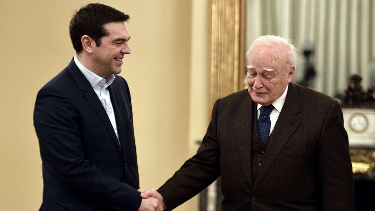De nieuwe Griekse premier Alexis Tsipras van Syriza schudt de hand met de Griekse president Karolos Papoulias. Beeld AFP