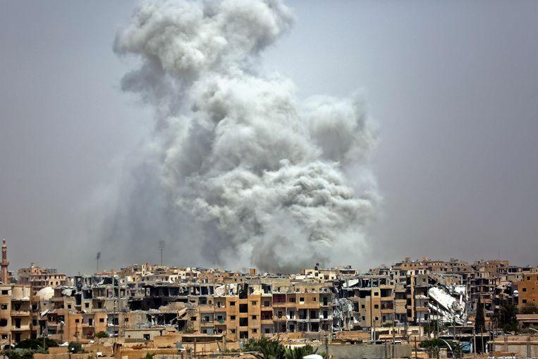 Rook stijgt op boven Raqqa, de stad die gold als de hoofdstad van IS, na een luchtaanval van de internationale coalitie in juli 2017. Beeld AFP