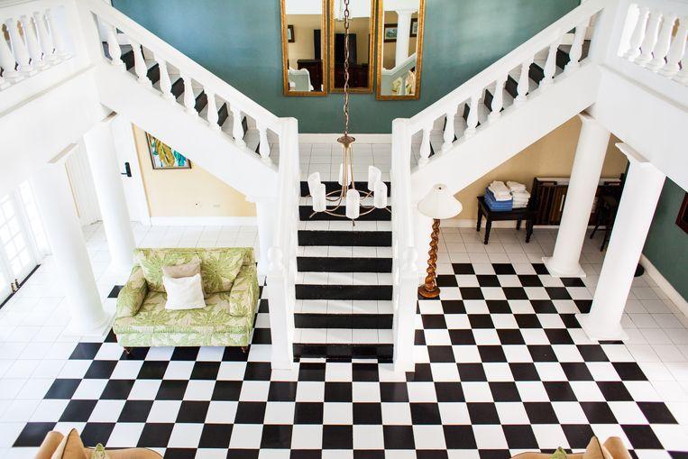 Op acht palmbomen van de oceaan ligt het hotel: een grote witte villa met een in damboordpatroon betegelde woonkamer. Beeld Ringo Gomez Jorge