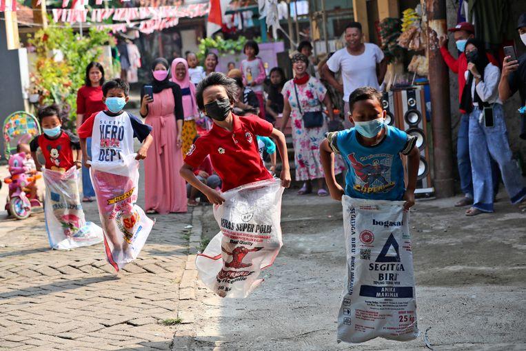 Kinderen spelen op straat tijdens de 17 augustus-viering. Beeld AP